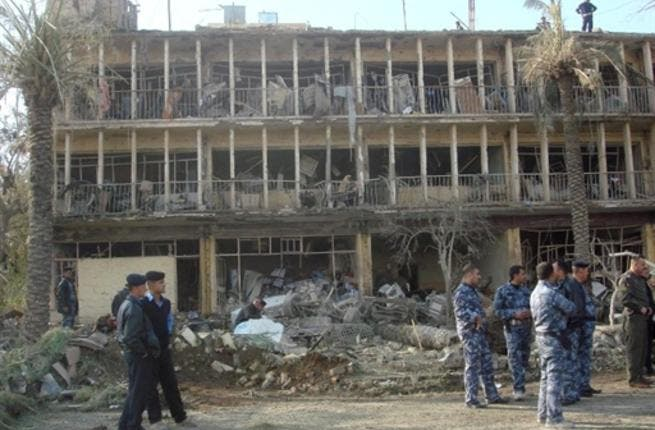 Members of Iraqi security forces gather next to the ruins of the Baquba headquarters of the Force Protection Service (FPS), where a suicide bomber rammed an ambulance packed with explosives killing 13 people.