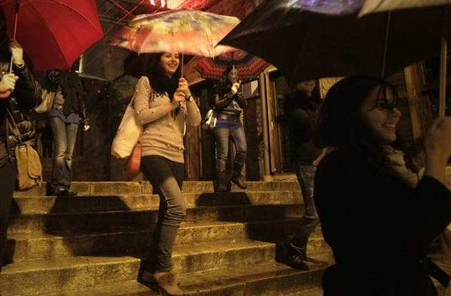 Lebanese women perform a dance in a street as rain approaches the mediterranean country after several months of drought.