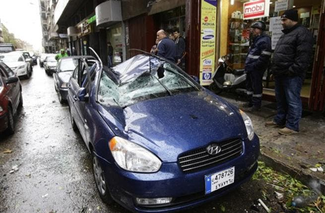 A car is damaged by a satellite dish which fell off the roof of a building in Beirut.