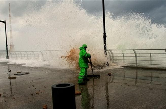 A municipality worker clears the mud as high waves rip off paving stones on Beirut's Mediterranean promenade.