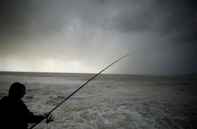 A Lebanese man fishes during a storm on the Mediterranean coast off the northern Lebanese port of Byblos.