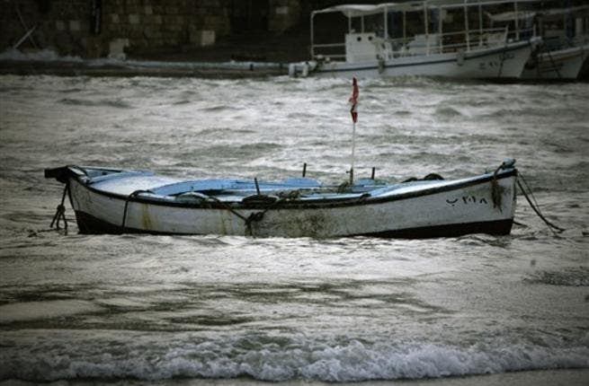 A fishing boat floats in wavy waters in the Lebanese ancient Mediterranean port of Byblos as heavy winds and rain whipped across Lebanon, grounding flights, knocking down billboards and causing nationwide traffic jams in the first winter storm to hit the country after months of drought.
