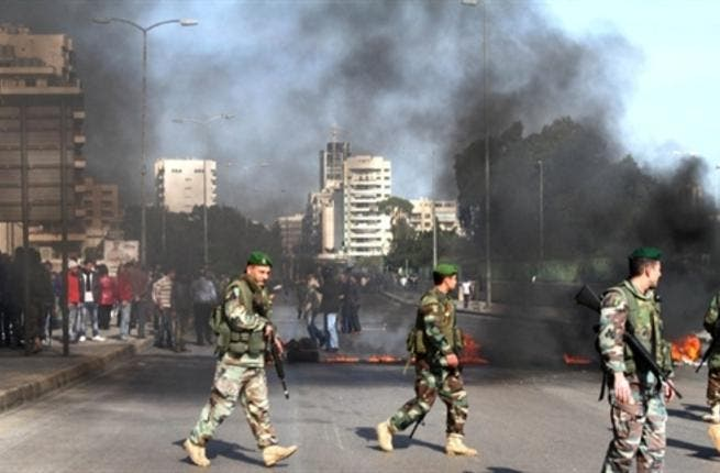 The Lebanese army are seen on the streets as supporters of the Future Movement burn tires in a neighborhood in the capital Beirut during a demonstration in support of the caretaker prime minister Saad Hariri.