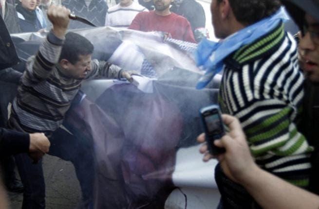Supporters of the Future Movement rip a poster of Lebanese MP Najib Mikati.