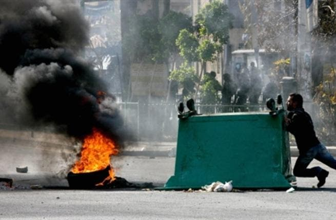 A garbage skips is pushed along a street as supporters of the Future Movement gather in a neighborhood in the capital Beirut during a demonstration in support of the caretaker prime minister Saad Hariri.