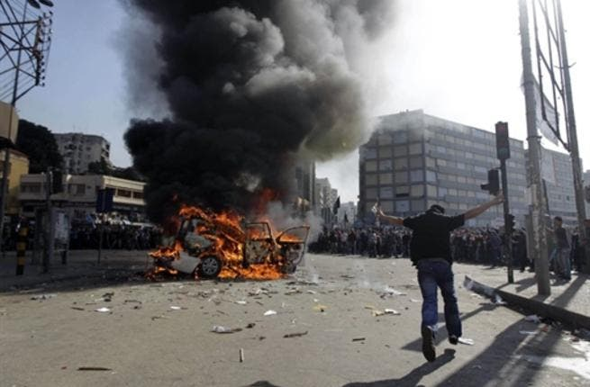 Supporters of the Future Movement gather as they watch the torched vehicle belonging to the Arabic language al-Jazeera satellite television station.