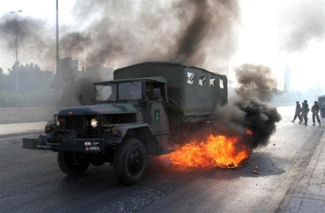 A Lebanese army truck drives through burning tires.