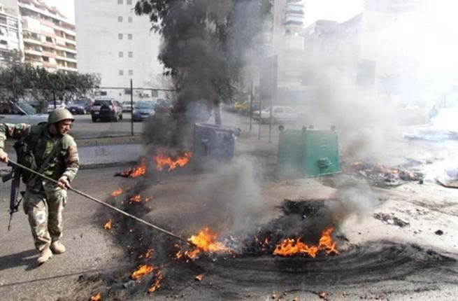 A Lebanese soldier disperses burning tires set alight by supporters of the Future Movement.