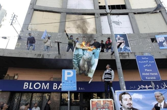 Supporters of the Future Movement torch a poster of Lebanese MP Najib Mikati during a demonstration in support of the caretaker prime minister Saad Hariri in the Sunni bastion coastal city of Tripoli north of Beirut.