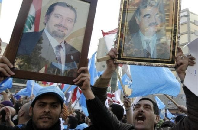 Holding up images of caretaker prime minister Saad Hariri (L) and his late father Rafiq (R) Lebanese supporters of the Future Movement.