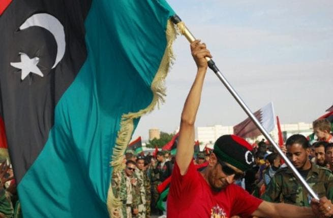A Libyan man waves his new national flag during a ceremony announcing the liberation for the country in the eastern city of  Benghazi. The new flag chimes in with the new chapter of hope for Libya. It also promises a return to Islamic values,  with the reinstatement of rights to marry more than one wife, as well as exclusively Islamic banking.