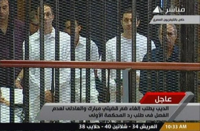 Egyptian former interior minister Habib al-Adly (R) stands along side Alaa (2nd R) and Gamal (L) Mubarak in a cage-like holding cell in the court room in the police academy.
