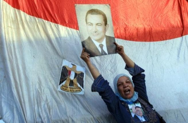 A supporter of ousted Egyptian President Hosni Mubarak holds his picture outside the police academy where Mubarak's trial is held on the outskirt of Cairo.