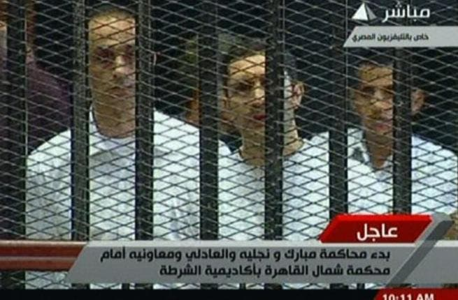 Alaa (C) and Gamal (L) Mubarak are seen in their 'family cage'. Bystanders observed Alaa to be clutching on to a Koran for much of the proceedings.
