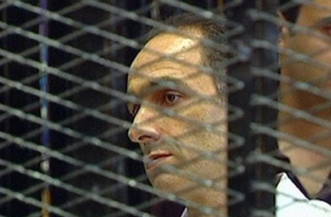Gamal Mubarak is seen in a holding cell on the first day of his trial along with his brother and father, ousted Egyptian president Mubarak and other government officials. Father-on-trial said to be fidgety & squirming, even playing with his nose; some have irreverently cited him as 'picking' it.
