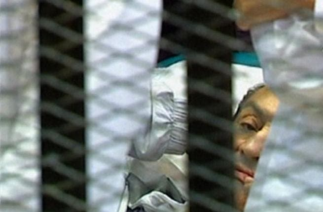 Egyptian former president Hosni Mubarak 'lying' hemmed into his 'cage' in a holding cell in the court room at the Cairo Criminal Court where he faces murder charges, is the first Arab ruler to appear in court in person in a historic moment for a region whose leaders are rarely held to account.