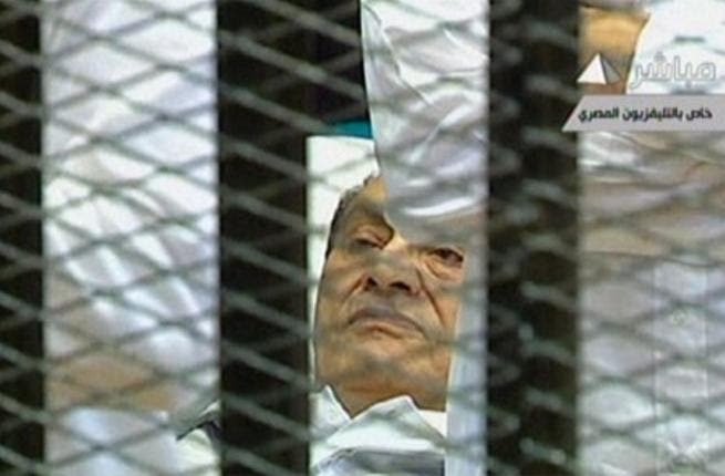 Egyptian former president Hosni Mubarak lies on a stretcher as he listens to the opening proceedings in a holding cell in the court room in the police academy. Comments emerging by the news-hungry public and media highlighted his dyed black hair- in spite of his invalid and ailing condition.