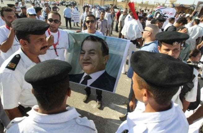 Egyptian supporters of former president Hosni Mubarak hold up his poster as they stand in front of the police on the opening day of his trial.