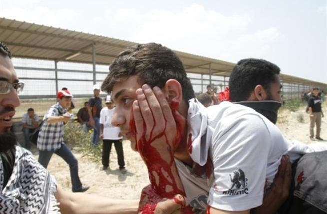 Gaza Guard: Palestinians carry away a wounded man as Israeli troops opened fire during on a massive march heading towards the Erez border crossing in the northern Gaza Strip. 45 injuries counted.