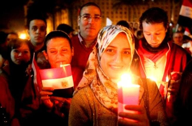 Thousands of Egyptian Muslims and Coptic Christians attend a celebration on New Year's eve in Tahrir Square in Cairo.