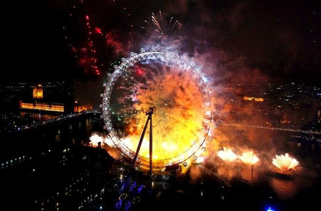 Fireworks light up The London Eye ferris wheel just after midnight in London, England.