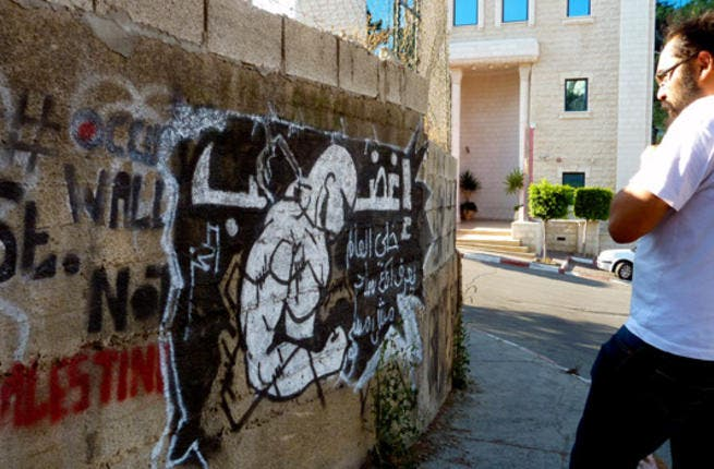"""""""Get mad — let the world know you are a magician, not bewitched"""" reads the text of street art in Ramallah by artist Hamza Abu Ayyash. Next to it is a stencil by artist Majd Abdel Hamid reading '#OccupyWallStNotPalestine' carrying a Twitter hashtag."""
