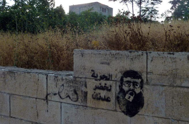 """""""Freedom for Khader Adnan"""" is written next to a stencil of Palestinian prisoner Khader Adnan with a lock over his mouth. Adnan became an icon after going on hunger strike for 66 days. He inspired not only other prisoners, but also activists who launched a campaign of stenciled tags on Ramallah walls and on Israel's West Bank separation wall."""