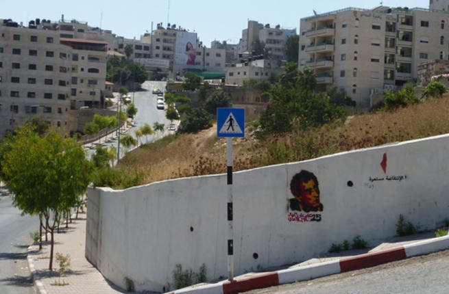 """A stencil tag of Naji al-Ali with the message """"25 years since al-Ali's assassination"""" is painted on this wall in Ramallah. Famous for having fathered Handala, al-Ali was also very critical of the Palestinian leadership, which many Palestinians believe was the reason behind the unsolved murder in 1987."""