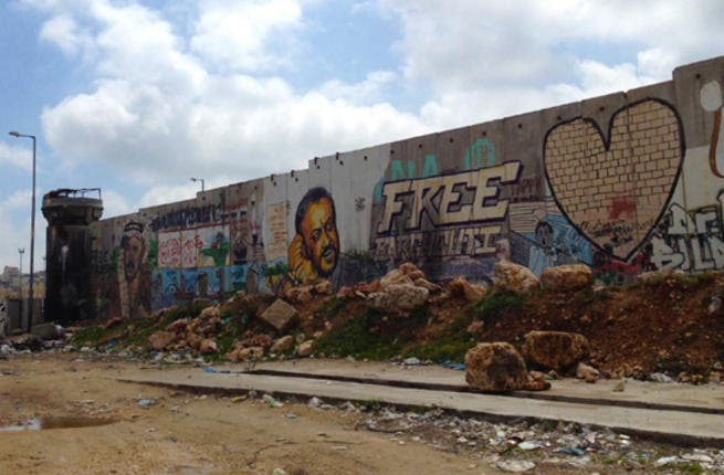 """Israel's West Bank wall is a great canvas for political art. At the Qalandia checkpoint by Ramallah, late Palestinian leader Yasser Arafat and jailed activist Marwan Barghouthi are portrayed on a segment of the eight-meter concrete wall. Most drawings are executed by foreign artists as many Palestinians refuse to """"beautify the wall."""""""
