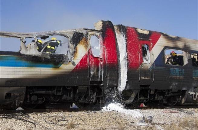 Israeli fire fighters spray water to extinguish the flames of a burning train coach near Kibbutz Shfaim, close to the Israeli city of Netanya.