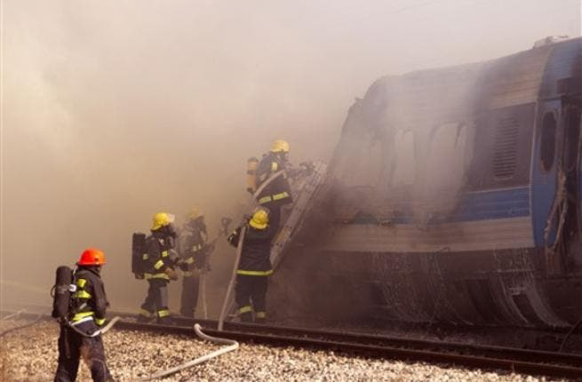 Israeli fire fighters spray water to extinguish the flames of a burning train coach near Kibbutz Shfaim, close to the Israeli city of Netanya about 15 kms north of Tel Aviv, after the passenger train cought fire, injuring almost 50 people, in an apparent accident.