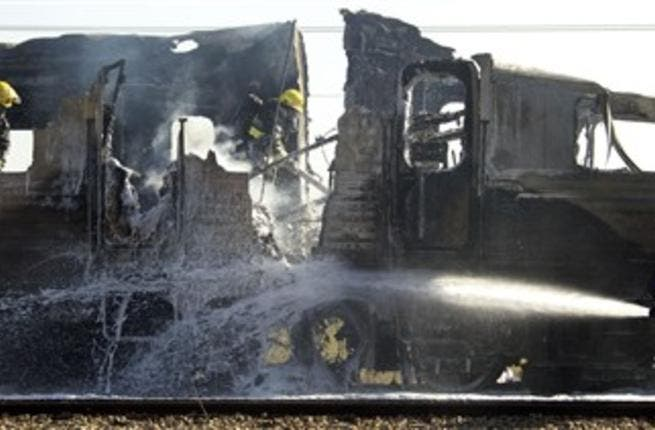 Israeli fire fighters spray water to extinguish the flames of a burning train coach.
