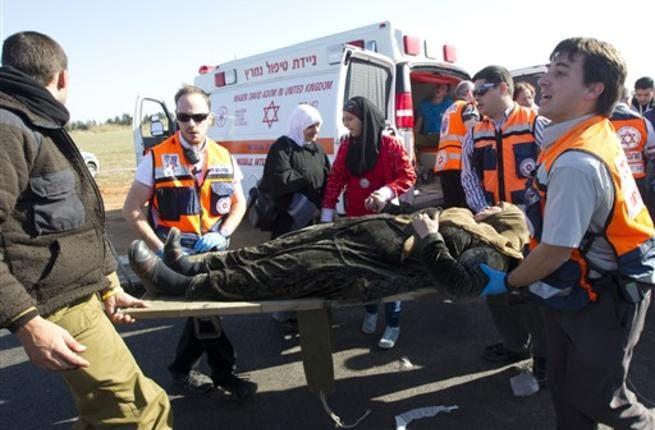 A wounded Arab Israeli woman is evacuated from a burning train coach by paramedics near Kibbutz Shfaim.