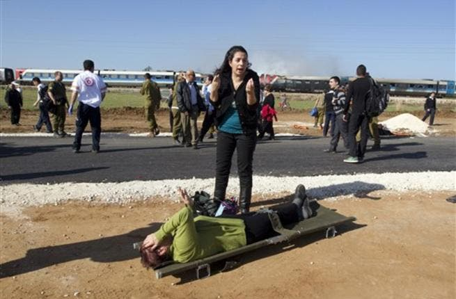 An Israeli woman reacts as she stands next to a wounded woman waiting to be evacuated on a stretcher at the scene of a train fire.