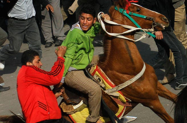 An opponent of embattled Egyptian president Hosni Mubarak (L) attacks a horse-riding pro-Mubarak supporter, pulling him off his horse during a clash between pro- and anti-Mubarak protesters.