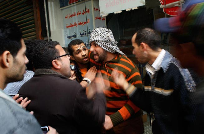 Egyptians regroup and argue about strategy in a side alley during a clash between pro- and anti-Mubarak protesters.