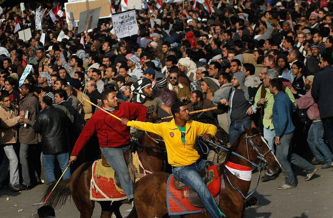 Supporters of embattled Egyptian president Hosni Mubarak ride horses through the melee during a clash between pro- and anti-Mubarak protesters.