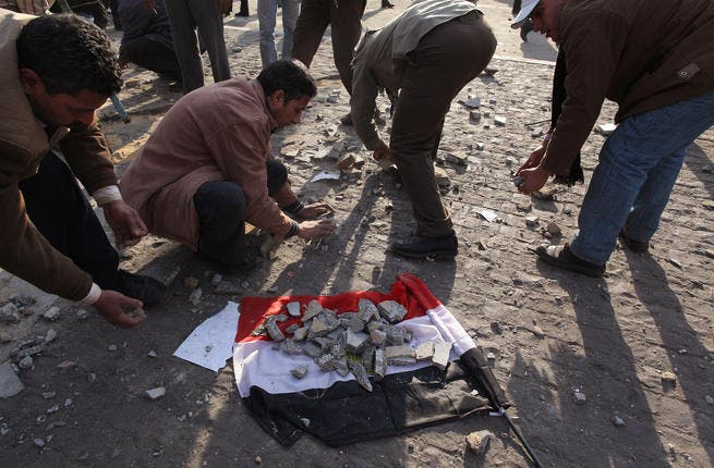 Anti-government protestors place broken paving stones on an Egyptian flag to throw at supporters of President Mubarak.