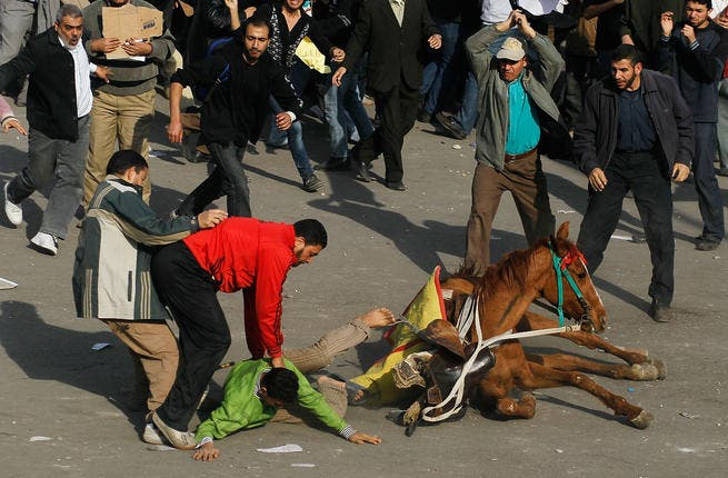 A supporter of embattled Egyptian president Hosni Mubarek is thrown from a horse.