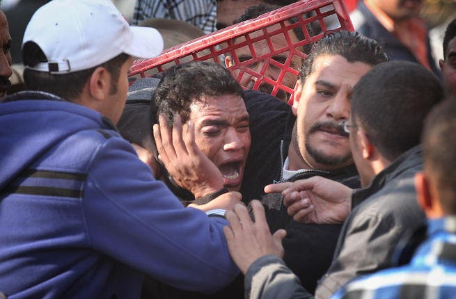 Anti-government protestors surround a supporter of President Mubarak after he was beaten in Tahrir Square.