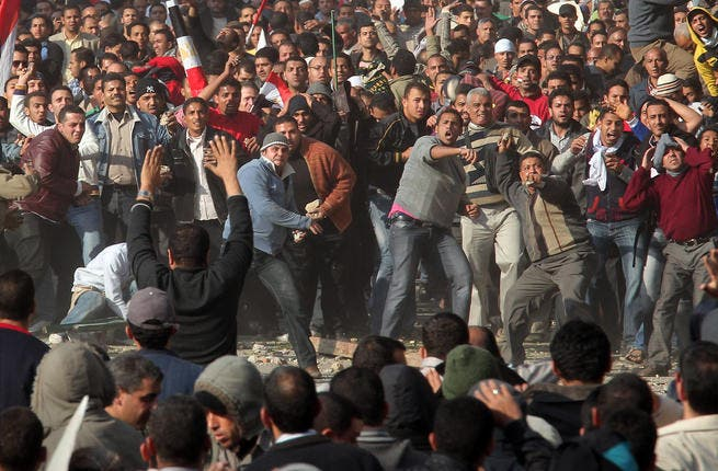 Anti-government protestors (front) clash with supporters of President Mubarak.