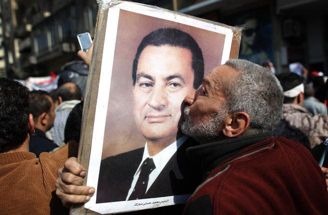 A man kisses a photograph of President Hosni Mubarak during a pro-government demonstration.