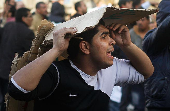 An opponent of embattled Egyptian president Hosni Mubarak tries to protect his head while calling for reinforcements during a clash between pro- and anti-Mubarak protesters.