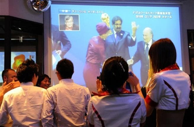 Japanese soccer fans watch television on Qatar's Emir being congratulated by FIFA President Sepp Blatter after they were announced as the 2022 World Cup host country at