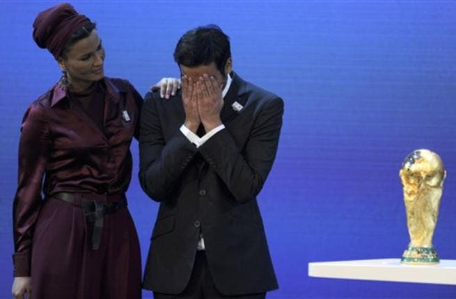 Chairman of Qatar 2022 Bid Committee Sheikh Mohammed bin Hamad Al-Thani (C) is comforted by Sheikha Moza bint Nasser Al-Missned on the podium with the World Cup trophy.