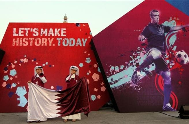 Qatari boys clad in traditional attire wave their national flag at Doha's traditional souk where people are gathering to follow FIFA's decision on who will host the 2022 World Cup.