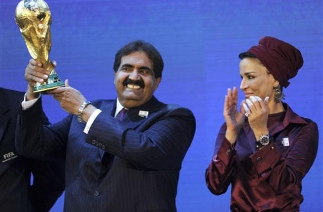 Emir of the State of Qatar Sheikh Hamad bin Khalifa Al-Thani (L) poses by his wife Sheikha Moza bint Nasser Al-Missned with the World Cup trophy after the official announcement that Qatar will host the 2022 World Cup.
