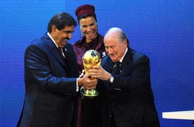 Fifa President Sepp Blatter (R) hands over the World Cup trophy to the Emir of the State of Qatar Sheikh Hamad bin Khalifa Al-Thani (L) and his wife.