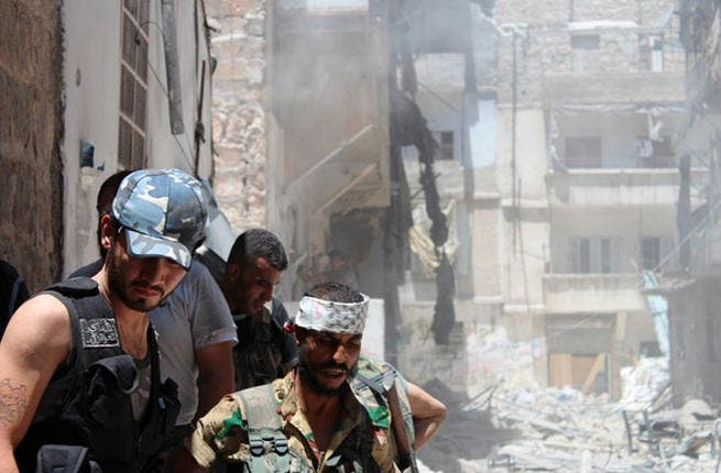 Ramadan snipers: On the first day of Ramadan, bombs and snipers are rife. Rebels descend on the building which they blew up to target a regime sniper taking shelter inside but who managed to escape in the Salaheddine district of the northern of Aleppo. (AFP PHOTO/SALAH AL-ASHKAR)