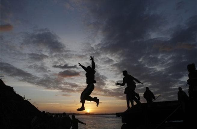 Palestinian boys jump from the top of a sand pile at the beach in Gaza City as they play outdoors during sunset, following storms and heavy rain that poured over the impoverished territory after months of drought.